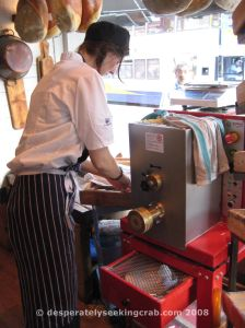 Employee making pasta at front of restaurant